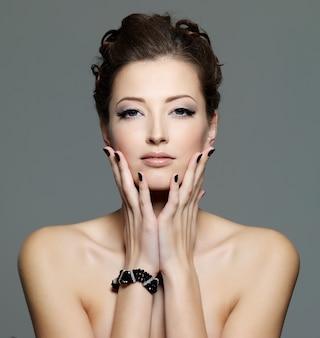 Mujer joven de glamour con uñas negras y maquillaje de ojos