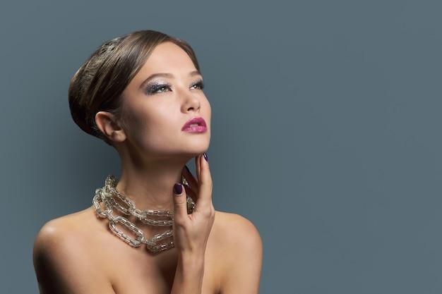 Mujer joven glamour sensual con maquillaje de noche, peinado, manicura