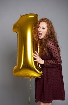 Mujer joven con globo dorado celebrando el primer cumpleaños de su empresa