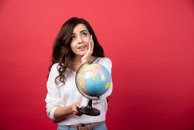 Mujer joven con globo soñando con viajar sobre fondo rojo. foto de alta calidad