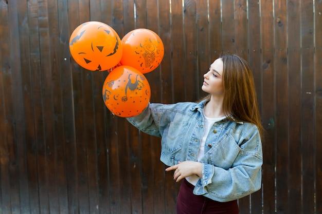 Mujer joven con globos inflables de halloween naranja sobre fondo marrón