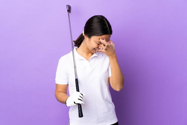 Mujer joven golfista sobre colorido con dolor de cabeza