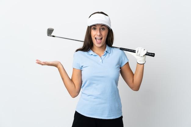 Mujer joven golfista sobre fondo blanco aislado con expresión facial conmocionada