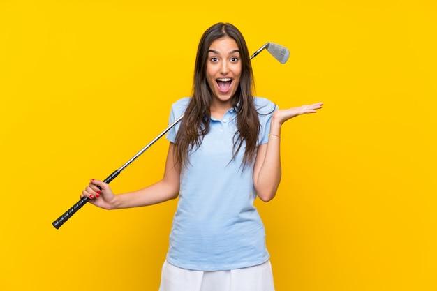 Mujer joven golfista sobre pared amarilla aislada con expresión facial sorprendida