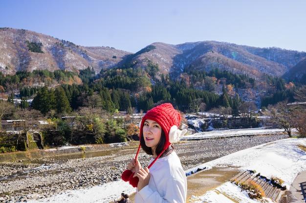 Mujer joven en una gorra roja con un hermoso paisaje ubicado en japón