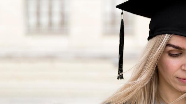Mujer joven con un gorro de graduación con espacio de copia