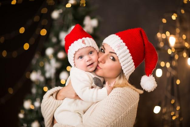 Mujer joven en gorro rojo de santa claus posando con little baby boy en gorro rojo contra las luces del árbol de navidad.