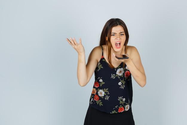 Mujer joven grabando mensaje de voz en el teléfono inteligente en blusa, falda y mirando irritado. vista frontal.