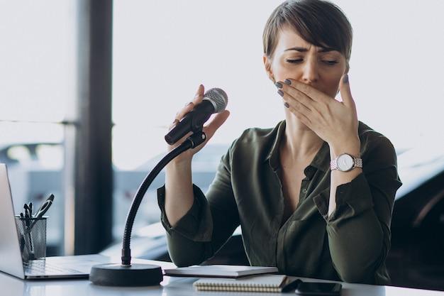 Mujer joven grabando voz actuando en el estudio