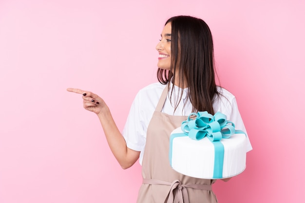 Mujer joven con un gran pastel apuntando hacia un lado para presentar un producto