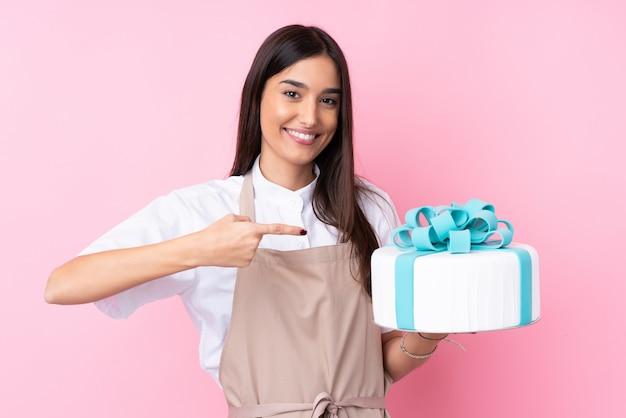 Mujer joven con un gran pastel y apuntándolo