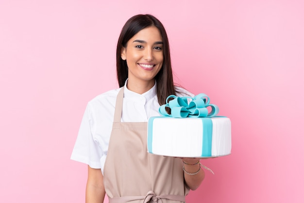 Mujer joven con un gran pastel sobre pared aislada sonriendo mucho