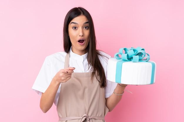 Mujer joven con un gran pastel sobre pared aislada sorprendida y apuntando al frente
