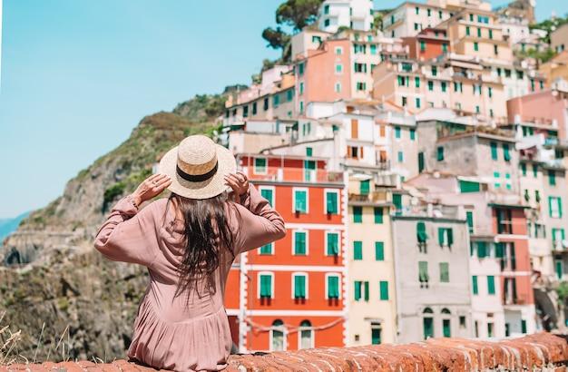 Mujer joven con gran vista en el pueblo viejo riomaggiore, cinque terre, liguria