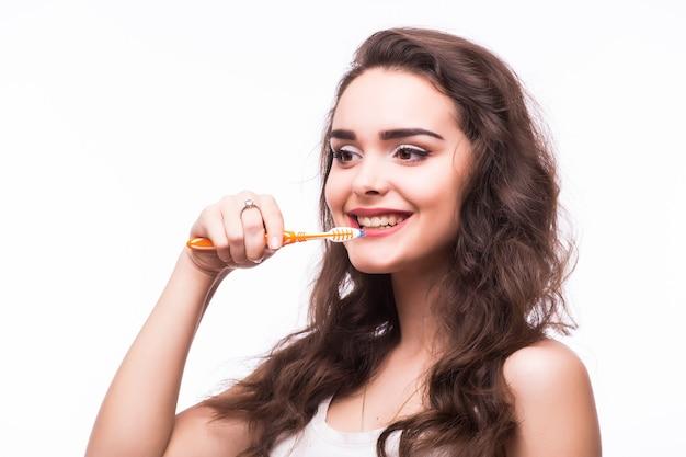 Mujer joven con grandes dientes sosteniendo cepillo de dientes, aislado sobre fondo blanco.
