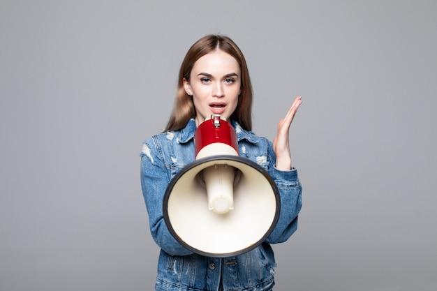 Mujer joven gritando a través de un megáfono para anunciar algo aislado en la pared gris