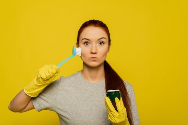 Mujer joven en guantes amarillos y cepillo de limpieza exfoliante para la piel.