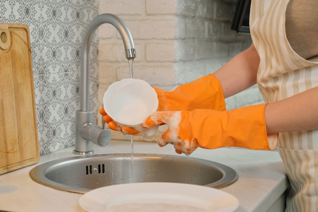 Mujer joven en guantes delantal lavando platos con esponja y detergente