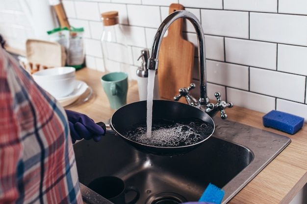 Mujer joven con guantes de goma lavando una sartén en la cocina.