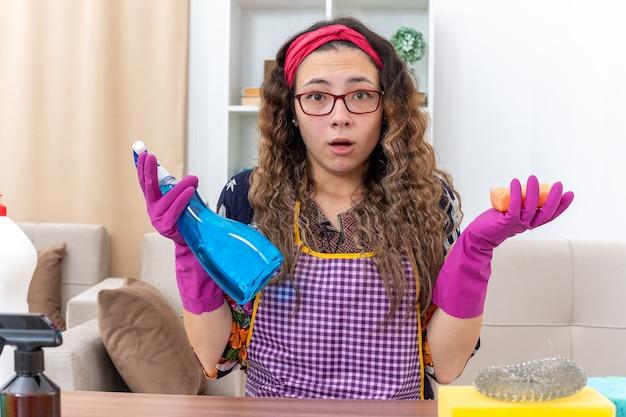 Mujer joven en guantes de goma con spray de limpieza y esponja surprsied sentado en la mesa con artículos de limpieza y herramientas en la sala de estar ligera