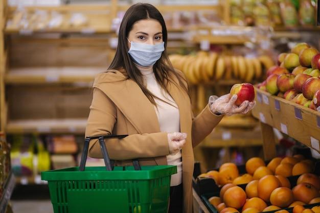 Mujer joven con guantes protectores y mascarilla sostiene hermosa manzana fresca en la mano. hermosa joven con canasta de alimentos eligiendo alimentos por stand con frutas. compras durante la cuarentena. covid-19