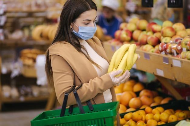 Mujer joven con guantes protectores y mascarilla sostiene hermosos plátanos frescos en la mano. hermosa joven con canasta de alimentos eligiendo alimentos por stand con frutas. compras durante la cuarentena. covid-19
