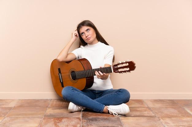 Mujer joven con guitarra sentada en el suelo con dudas y con expresión de la cara confusa
