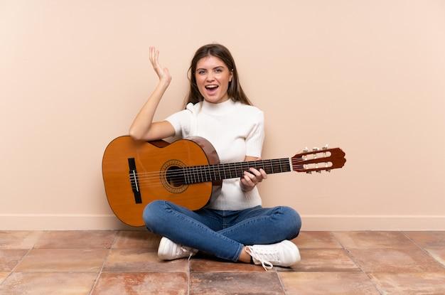Mujer joven con guitarra sentada en el suelo infeliz y frustrada con algo