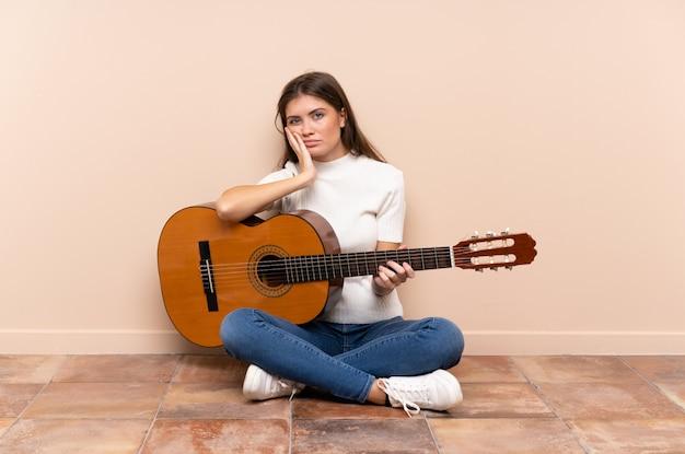 Mujer joven con guitarra sentada en el suelo infeliz y frustrada