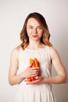 Mujer joven en una habitación luminosa con una zanahoria