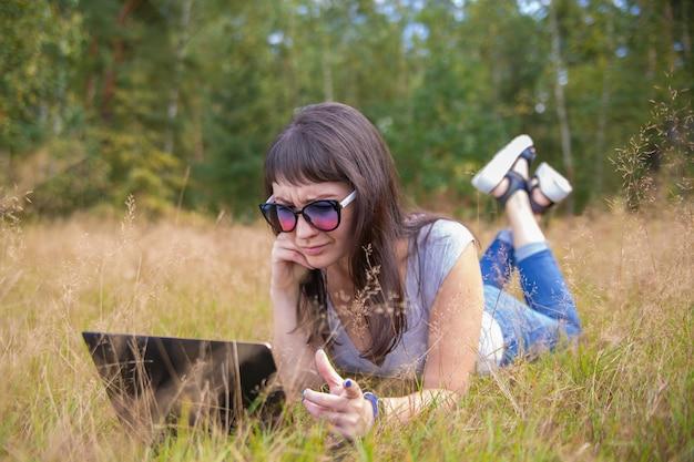 Mujer joven hablando emocionalmente el teléfono y mirando a un ordenador portátil mujer autónoma trabaja en un