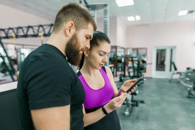 Mujer joven hablando con entrenador personal en gimnasio