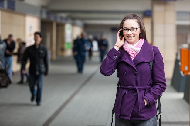 Mujer joven hablando por móvil en la estación de tren