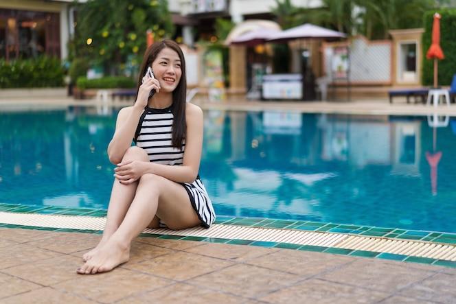 Mujer joven hablando por teléfono móvil en la piscina