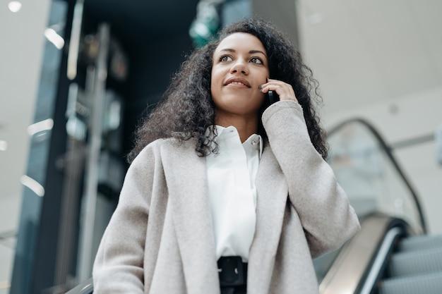 Mujer joven hablando por su teléfono inteligente de pie en los escalones de la escalera mecánica