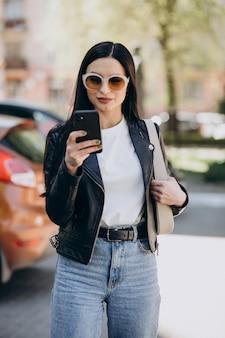 Mujer joven hablando por teléfono y caminando en la ciudad