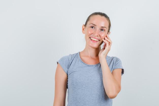 Mujer joven hablando por teléfono celular en camiseta gris y mirando contento. vista frontal.