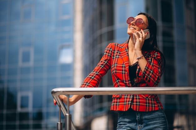Mujer joven hablando por teléfono en el centro de la oficina