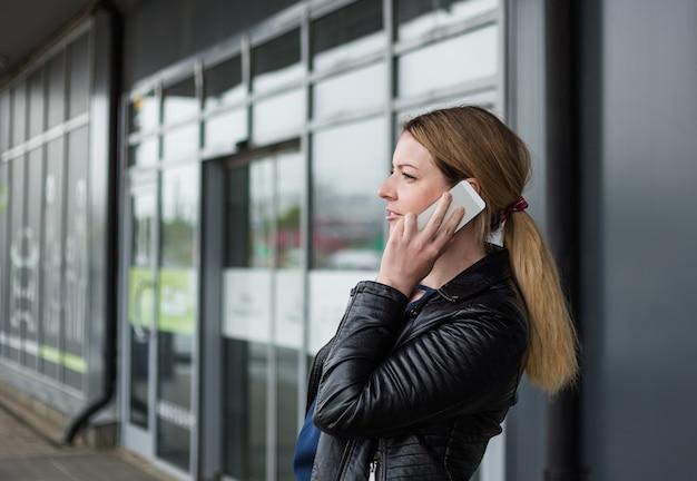 Una mujer joven está hablando por teléfono cerca de un centro comercial.