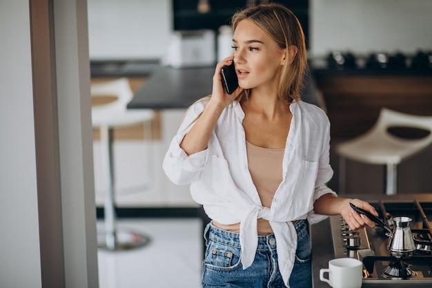 Mujer joven hablando por teléfono y haciendo café por la mañana
