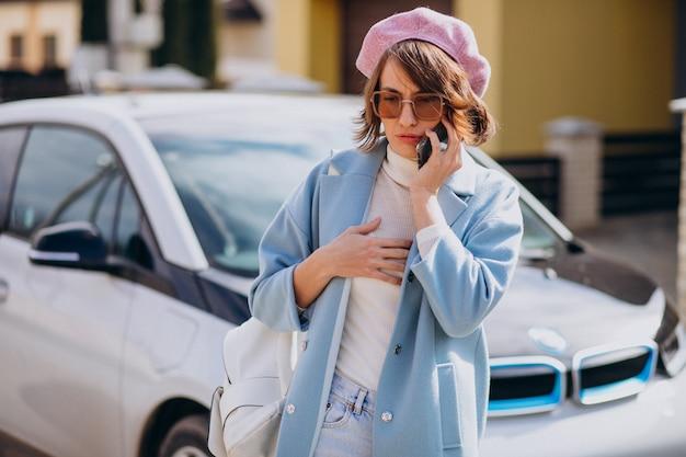 Mujer joven hablando por teléfono junto a su auto eléctrico