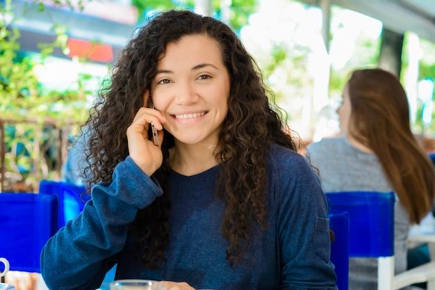 Mujer joven hablando por teléfono móvil en la cafetería.