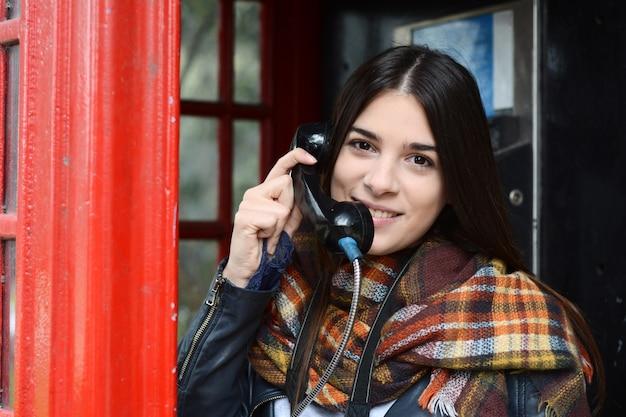 Mujer joven hablando por teléfono en el teléfono de caja roja.