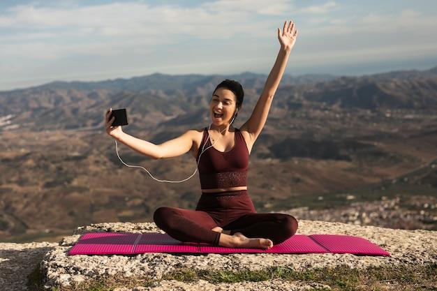 Mujer joven hablando videollamada mientras hace yoga