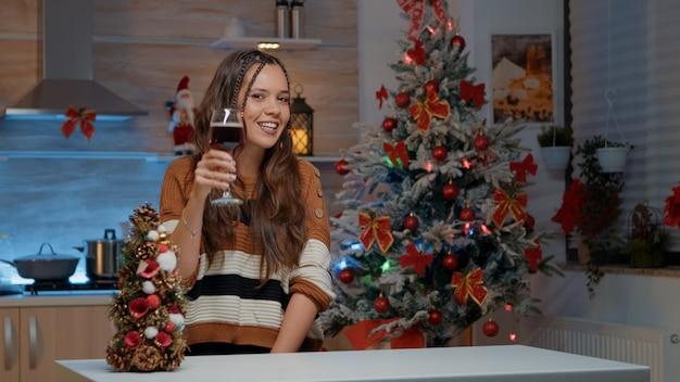 Mujer joven hablando por videollamada sosteniendo una copa de vino