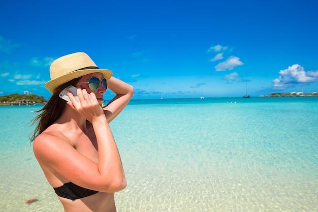 Mujer joven hablar por teléfono en la playa tropical