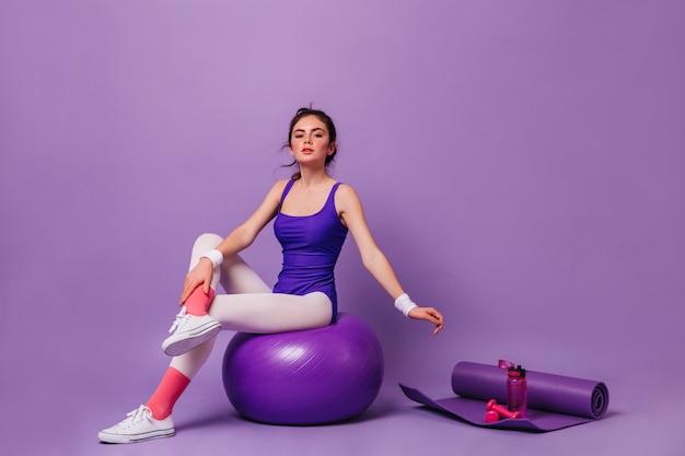 Mujer joven hace aeróbicos en pared púrpura