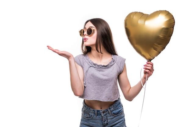 Mujer joven hace un beso al aire con un globo de corazón en forma de corazón