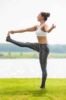 Mujer joven hace pose de yoga en el parque por la mañana con luz solar