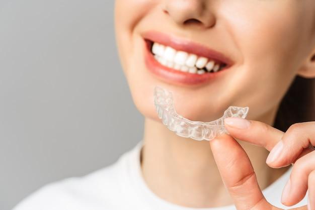 Una mujer joven hace un procedimiento de blanqueamiento de dientes en casa bandeja de blanqueamiento con gel